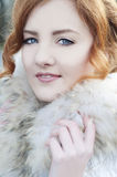 Beautiful redheaded woman in fur coat Stock Images