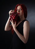 Beautiful redheaded woman with grape Royalty Free Stock Image