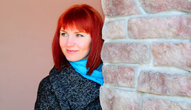 Beautiful redheaded young woman. Portrait of a beautiful redheaded young woman against a wall Royalty Free Stock Photos
