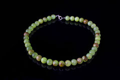 Beautiful, refined necklace of green onyx beads on a black background royalty free stock images
