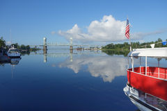 Beautiful reflection of Cape Fear Memorial bridge. A still morning reflects white clouds and the Cape Fear Memorial Bridge on the Cape Fear River in Wilmington Royalty Free Stock Photography