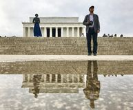 Beautiful reflection after rain in Washington DC. Here 2 person staring in front of the Lincoln memorial with different position stock images