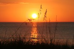 ORANGE GLOW AS THE SUN SETS OVER WATER Royalty Free Stock Photos