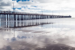 Beautiful reflection of a wharf and cloudy sky. stock images