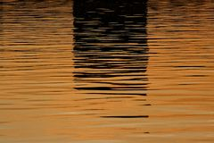 Beautiful reflections on the water before sunset in orange and dark colors – Moscow river stock photo