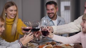 Beautiful relatives clinking glasses with wine and juice while celebraring Thanksgiving day