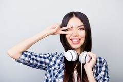 Beautiful relaxed asian girl with dark long hair, toothy smile i. S giving a wink, showing v-sign and listening to her favourite song, isolated on grey Royalty Free Stock Photos