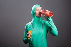 Beautiful relaxed athlete muslim woman in green hijab or islamic. Sport wear standing, resting, holding orange bottle and drinking with closed eyes. indoor royalty free stock photo