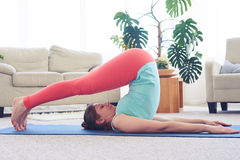 Beautiful relaxed girl in plow asana on yoga mat Royalty Free Stock Images