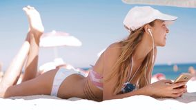 Beautiful relaxed slim sexy tanned woman in bikini and white cap with navy blue Union Jack British flag is lying on the. Beach on a white sand under big white stock footage