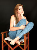 Beautiful Relaxed Thoughtful Young Woman Sitting in a Chair. A DSLR royalty free image, of attractive young woman sitting in directors chair with feet up and Stock Image