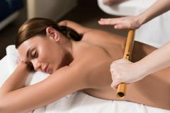 beautiful relaxed woman having bamboo massage stock images