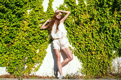 Beautiful relaxed woman with long chestnut hair standing at the wall twined with ivy enjoying the sunshine Stock Photo