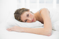 Beautiful relaxed woman lying on her bed under the cover Stock Photos
