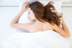 Beautiful relaxed woman lying and sleeping on bed in bedroom Stock Image