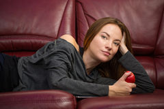 Beautiful relaxed woman lying on sofa and eating apple Stock Photography