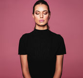 Beautiful relaxed woman with perfect skin and makeup. Portrait of caucasian female model standing with her eyes closed against pink background. Beauty portrait Stock Photo