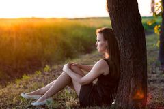 Beautiful relaxed woman sitting near the tree Royalty Free Stock Photography