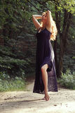 Beautiful relaxed woman in sundress in summer forest. Beautiful relaxed  woman in sundress in sunny summer forest Royalty Free Stock Photo