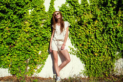 Beautiful relaxed woman in white romper, keds and trendy round mirrored sunglasses standing at the wall entwined with ivy. Young beautiful relaxed woman with stock images