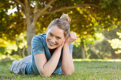 Beautiful relaxed young woman lying on grass at park Stock Photos