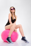 Beautiful relaxed young woman posing on pink fitball. Beautiful attractive confident relaxed young woman in black leotard and pink sunglasses posing on pink Stock Image