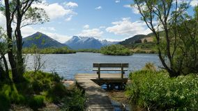 Empty bench in shore of the lake Wakatipu in scenic Glenorchy area, New Zealand stock photography