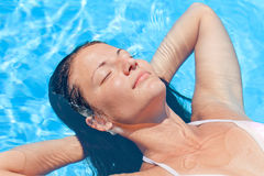 Beautiful relaxing woman. Beautiful young woman relaxing in the swimming pool Royalty Free Stock Photo