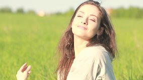 Beautiful relaxing woman sitting on the grass  and enjoying fres stock video footage