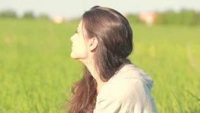 Beautiful relaxing woman sitting on the grass and enjoying fres