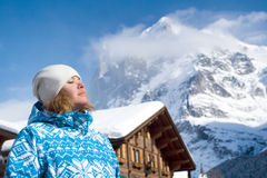 Beautiful relaxing young woman. Swiss alps. Beautiful young woman looking up. There are a top of alpine mountain summit on the background and a house(hotel) Stock Image