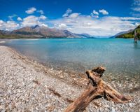 Beautiful and remote alpine scenery at Kinloch, NZ. Low angle View from the rocky Dart river banks at Kinloch with mountain range and wooden piers in the Stock Photography