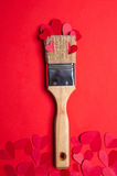 Beautiful repair on the valentin's day. New paintbrush decorated paper red hearts on a red background Stock Image