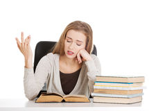 Beautiful resigned student woman with stack of books. Royalty Free Stock Photography