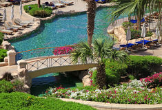Beautiful resort swimming pool with sun chairs, bridge and flowe Royalty Free Stock Image