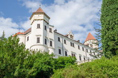 Beautiful restored white castle with red tiles and blue sky in Czech Republic. Surrounded by green gardens Stock Image