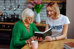 Beautiful retired woman having heart-to-heart talk with young-adult fair-haired lady. Having heart-to-heart talk. Beautiful grey-haired retired women wearing stock images
