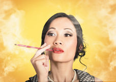 Beautiful reto lady smoking on yellow background Royalty Free Stock Images