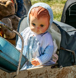 Beautiful retro baby doll in baby carriage at flea market Royalty Free Stock Photos