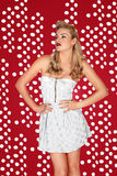 Beautiful retro blonde model in a miniskirt. Beautiful retro blonde fashion model posing in a stylish white miniskirt against a rich red studio background stock image