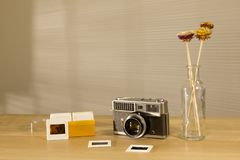 Beautiful retro camera and slides film on the table with morning light royalty free stock photos