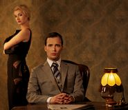 Beautiful retro couple. Man in suit  with women behind him Royalty Free Stock Image