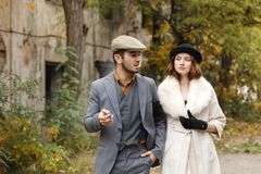A beautiful retro gangsters couple are walking. The guy smokes a cigar and looks at the girl. Outdoors. royalty free stock image