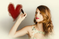 Beautiful retro girl painting red love heart Stock Photography
