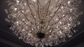 Beautiful retro luxury crystal strass chandelier isolated on a white wall of the restaurant. stock footage