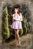 Beautiful retro maid with hedge clippers in garden. Stylish woman in the garden holding pruning shears in a purple mini dress Royalty Free Stock Photos