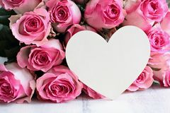 Beautiful Soft Pink Rose with Blank Wooden Heart Background. Beautiful retro soft pink rose flower background with wooden heart and room for text royalty free stock photography