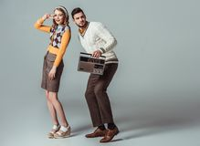 Beautiful retro styled couple dancing with vintage radio. On grey stock photos