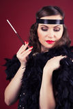 Beautiful retro woman holding mouthpiece against wine red backgr Stock Image