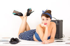 Beautiful retro young girl wearing blue vintage. Beautiful young girl with hand under her chin in retro clothes and hairstyle representing pinup style lying on stock images